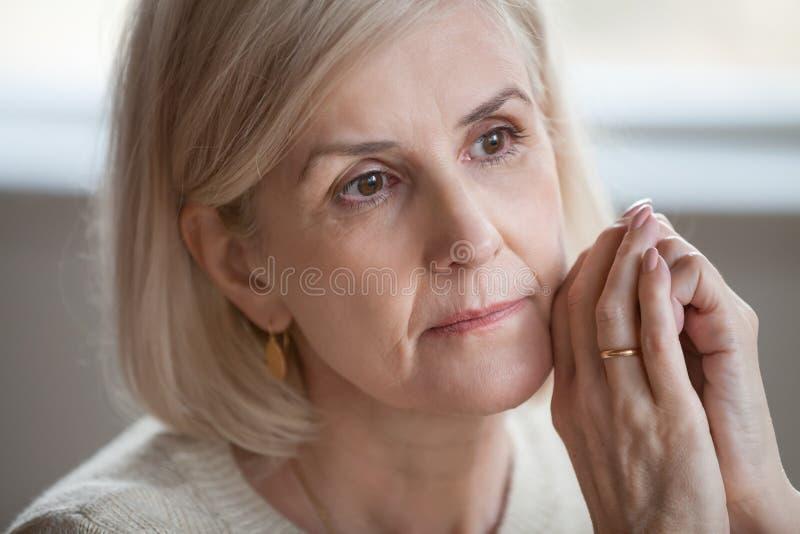 Sluit portret omhoog droevige nadenkende aantrekkelijke oude vrouw stock foto