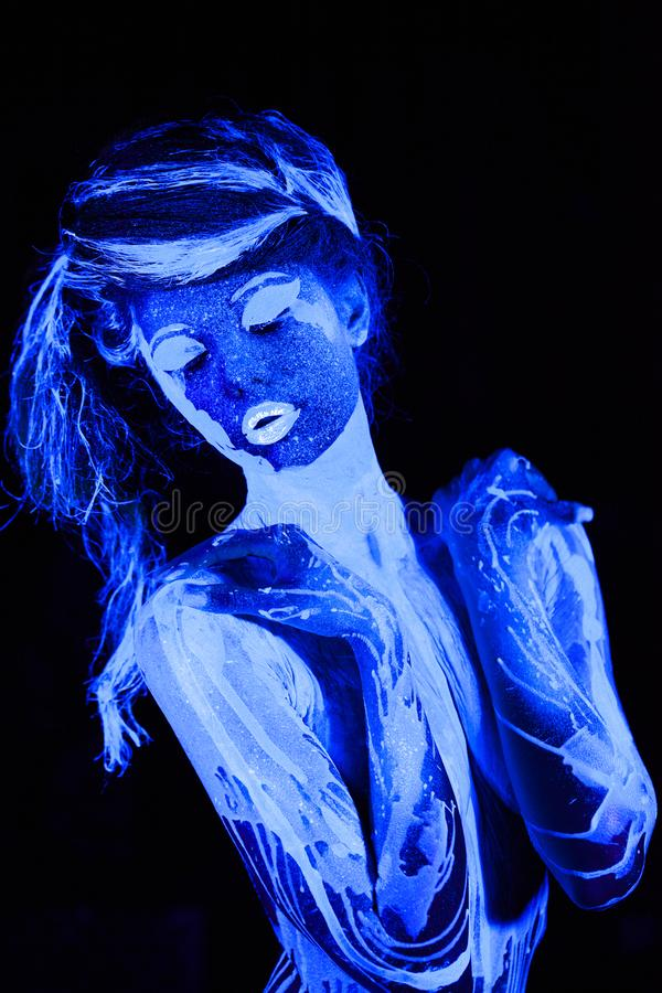 Sluit portret omhoog jong die meisje in ultraviolette verf wordt geschilderd stock foto's