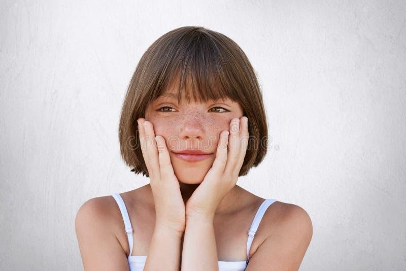 Sluit portret van aanbiddelijk freckled meisje met bobbed kapsel, die omhoog haar handen op wangen houden, die dromerige uitdrukk stock foto's
