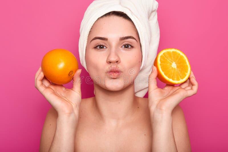 Sluit portret van aantrekkelijke vrolijke vrouw houdt oranje plakken, houdt omhoog lippen gevouwen, draagt handdoek en de naakte  royalty-vrije stock afbeelding