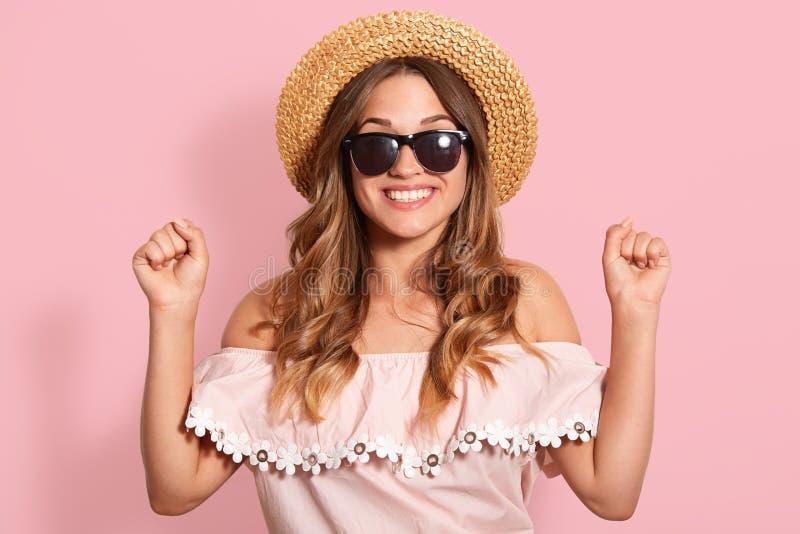 Sluit portretal uitrusting, omhoog strohoed en zwarte zonnebril, dichtklemmend haar handen in vuisten over roze achtergrond, die  royalty-vrije stock foto