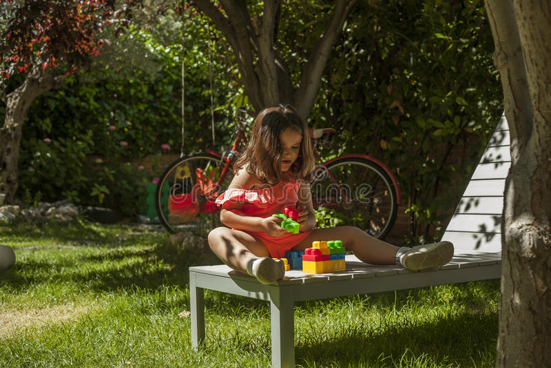 Sluit portretmeisje omhoog het spelen met plastic bouw binnen speelgoed royalty-vrije stock foto's