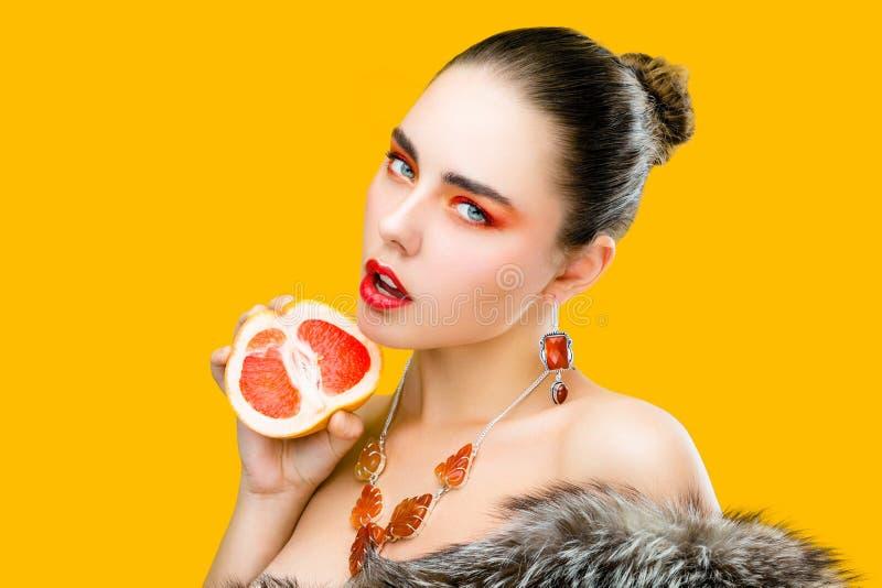 Sluit schoonheidsportret van jonge vrouw met beroeps maken omhoog omhoog het houden van in hand halve granaatappel royalty-vrije stock fotografie