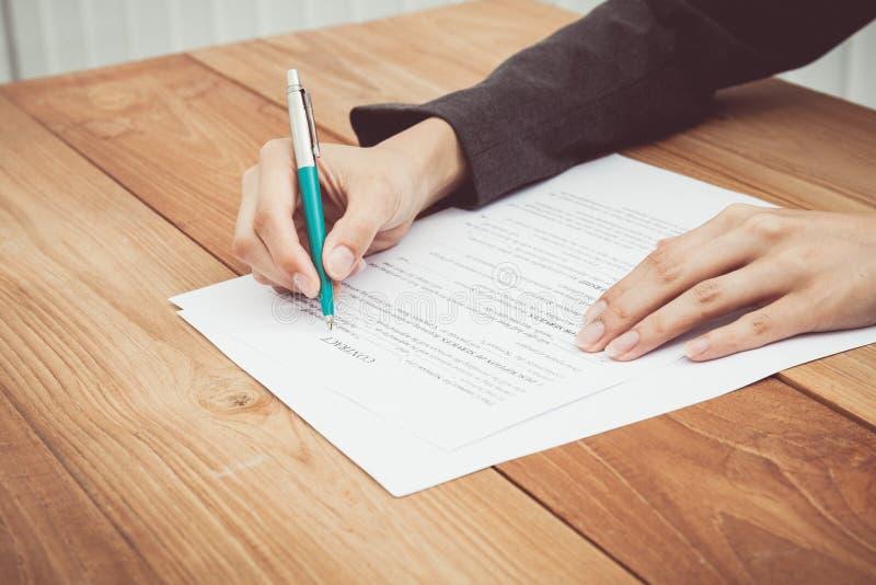 Sluit schot van een menselijk hand het schrijven contract royalty-vrije stock afbeelding