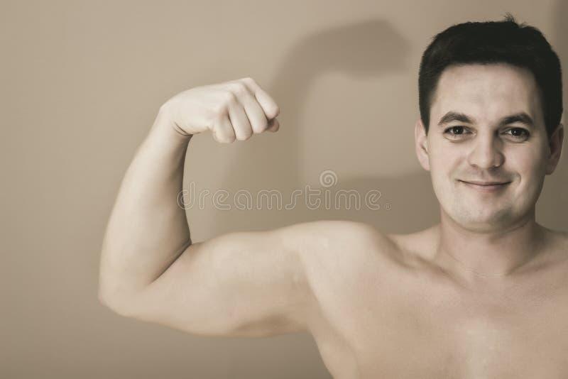 Sluit schot van een topless mens die zijn rechtse spieren, op zijn gezichtsglimlach tonen stock afbeeldingen