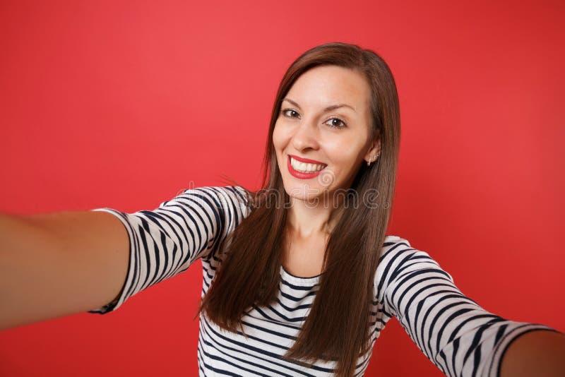 Sluit selfie omhoog schot van mooie glimlachende jonge vrouw in toevallige gestreepte die kleren op heldere rode muurachtergrond  royalty-vrije stock fotografie