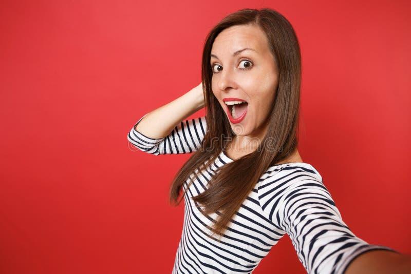 Sluit selfie omhoog schot van verbaasde jonge vrouw in gestreepte kleren die mond het brede open verrast kijken houden geïsoleerd royalty-vrije stock foto