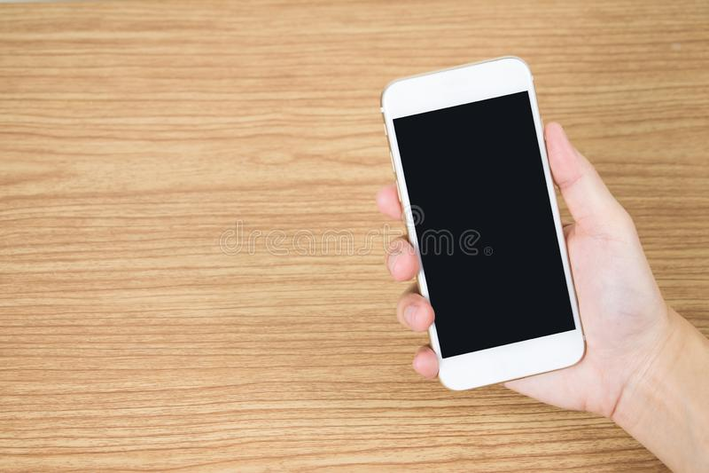 Sluit tot de hand houdend mobiel op de oude houten lijst in de ruimte stock foto's
