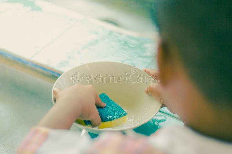 Sluit tot handen van Kleuterschoolstudent schoonmaakt schotel stock afbeelding