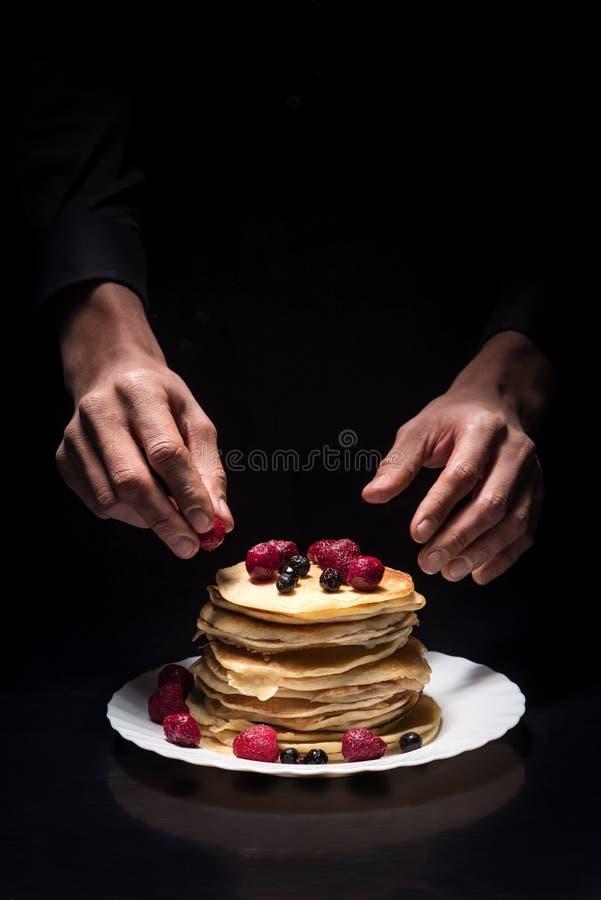 Sluit van bemant omhoog handen verfraaiend de pannekoeken royalty-vrije stock foto