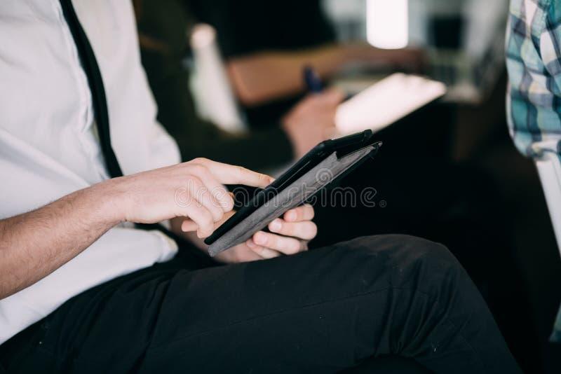 Sluit van de jonge mens met tablet maken omhoog bericht bij presentatie of vergadering van bureauteam groepswerk stock afbeeldingen