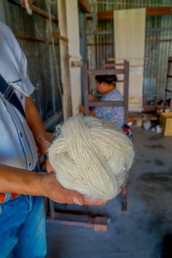 Sluit van een mensenholding in zijn hand omhoog een stuk van wol om aan weefgetouw de sjaalkleding van productiewhool in Nepal te royalty-vrije stock foto