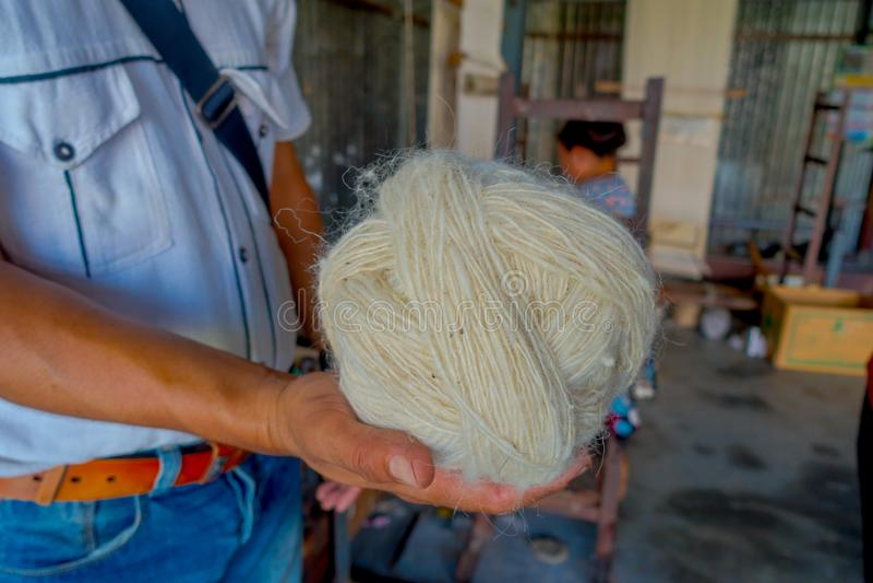 Sluit van een mensenholding in zijn hand omhoog een stuk van wol om aan weefgetouw de sjaalkleding van productiewhool in Nepal te stock fotografie
