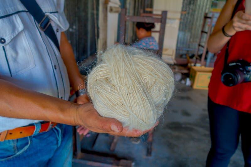 Sluit van een mensenholding in zijn hand omhoog een stuk van wol om aan weefgetouw de sjaalkleding van productiewhool in Nepal te royalty-vrije stock foto's