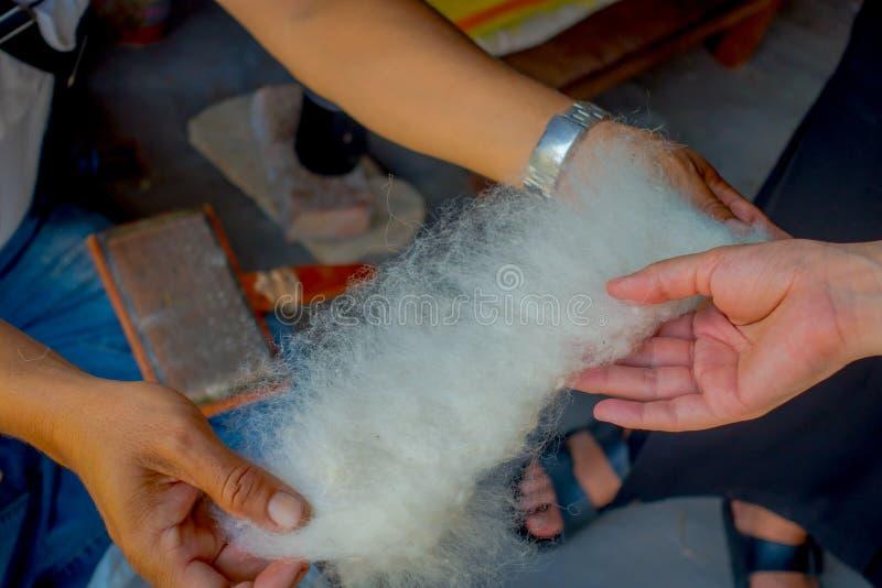Sluit van een mensenholding in zijn hand omhoog een stuk van wol om aan weefgetouw de sjaalkleding van productiewhool in Nepal te royalty-vrije stock afbeelding
