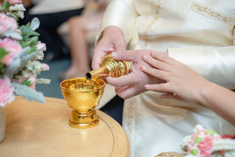 Sluit van een paar van het handhuwelijk gieten omhoog water van toewijding, het huwelijk van Thailand stock foto