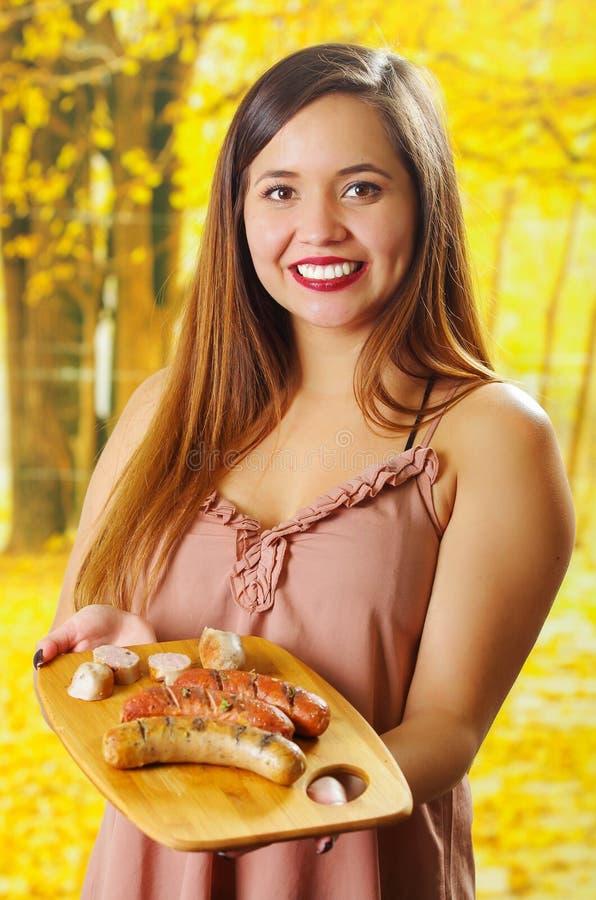 Sluit van glimlachende mooie jonge vrouwenholding in haar handen omhoog geroosterde worsten op houten scherpe raad, BBQ in stock foto's