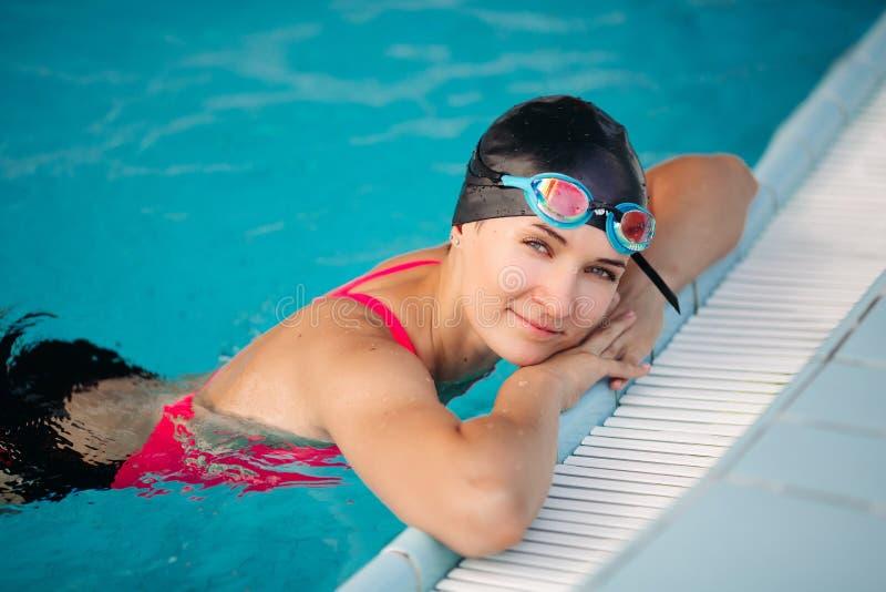 Sluit van het mooie jonge vrouw leunen langs indient zwembad, omhoog het rusten en het glimlachen stock afbeelding