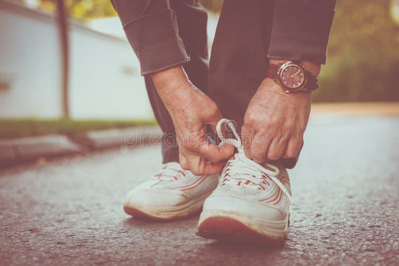 Sluit van hogere vrouw overhandigt omhoog bindende tennisschoenen royalty-vrije stock foto's