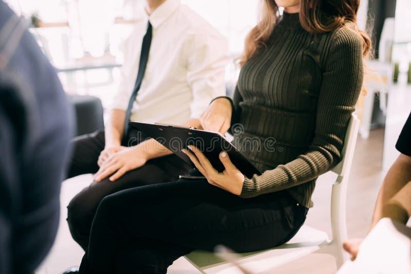 Sluit van jonge vrouw maken omhoog bericht in notitieboekje op vergadering van het teambuilding van het werk of presentatie in bu stock foto's