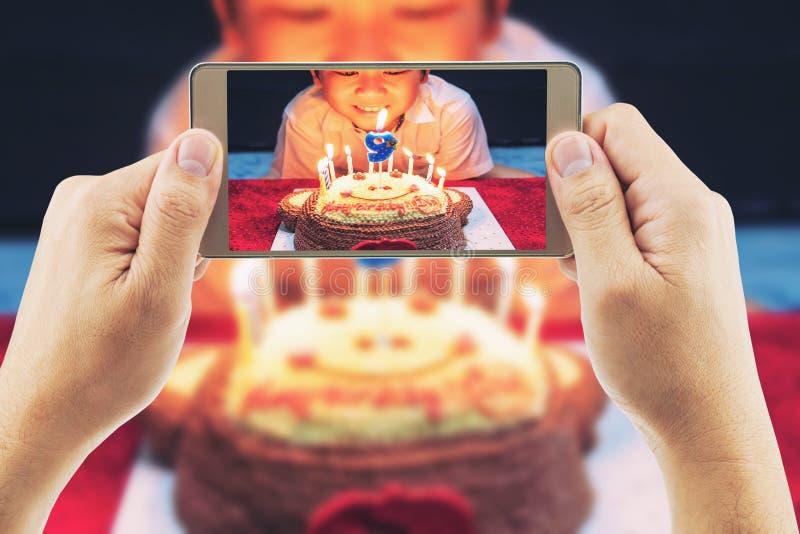 Sluit van mensen opnemen foto van een jongen klaar te blazen royalty-vrije stock afbeeldingen