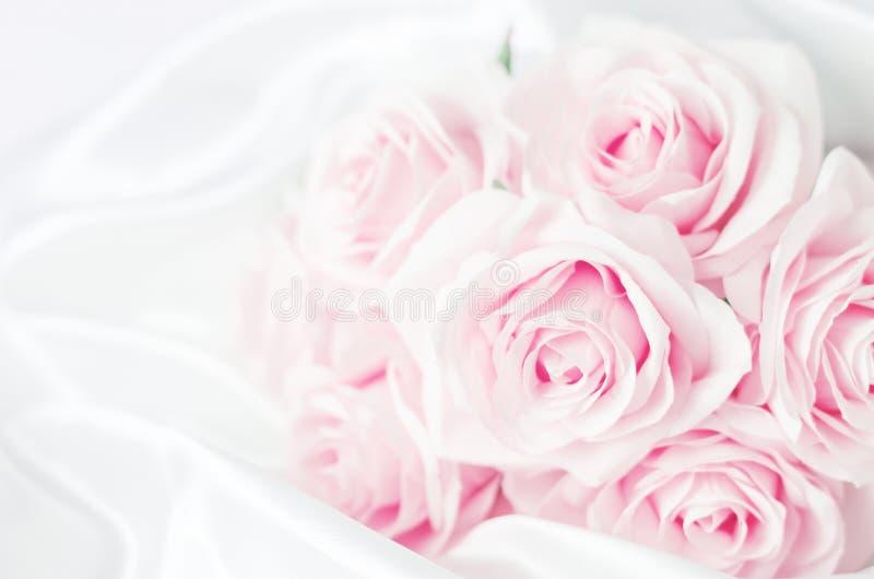 Sluit van roze purper steeg bloemenboeket terug op wit satijn stock foto's