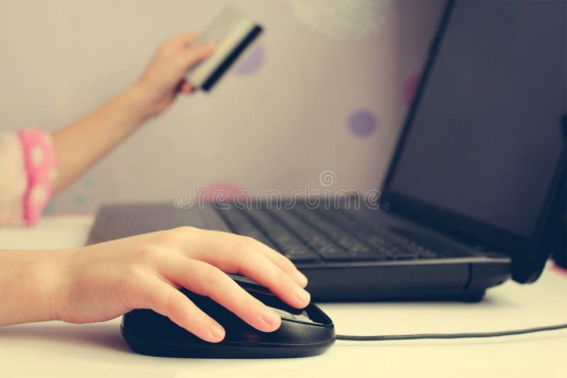 Sluit van vrouwelijke hand op computermuis en holding omhoog een creditcard royalty-vrije stock foto's