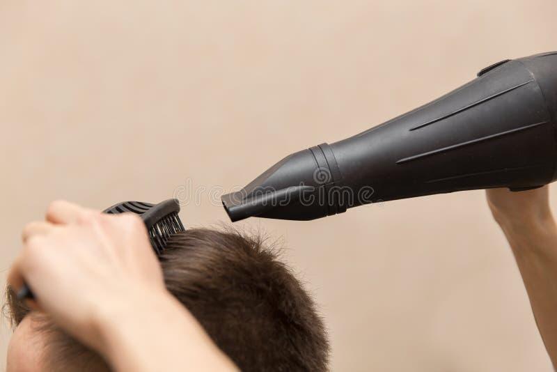 sluit van vrouwelijke kapper omhoog het drogende haar van haar mannelijke klant in haar herenkapper royalty-vrije stock foto's