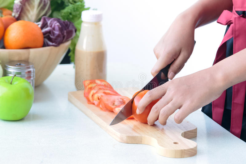 Sluit van vrouwen` s chef-kok overhandigt omhoog kokende groentensalade stock afbeelding