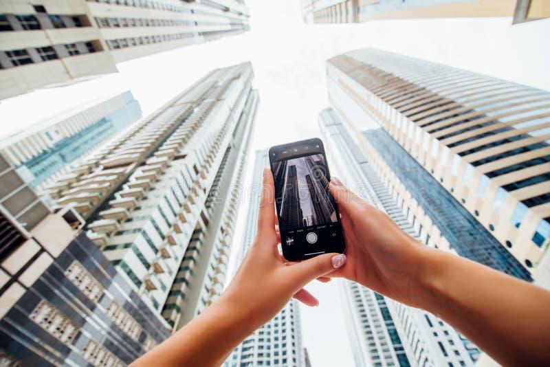 Sluit van vrouwenhanden opnemen telefoon op iphone van skycrapers in moderne arhitecturestad Lage hoekmening stock afbeelding