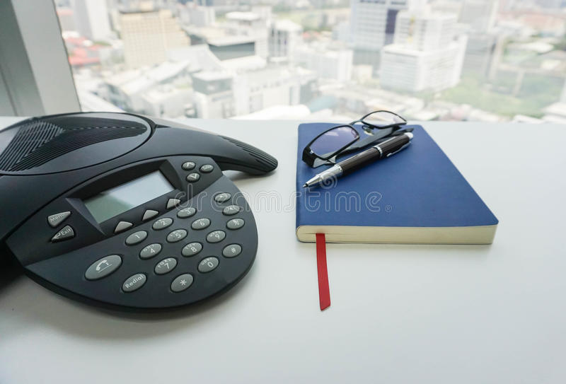 Sluit voip IP omhoog conferentietelefoon met notitieboekje en oogglazen voor vergadering royalty-vrije stock fotografie