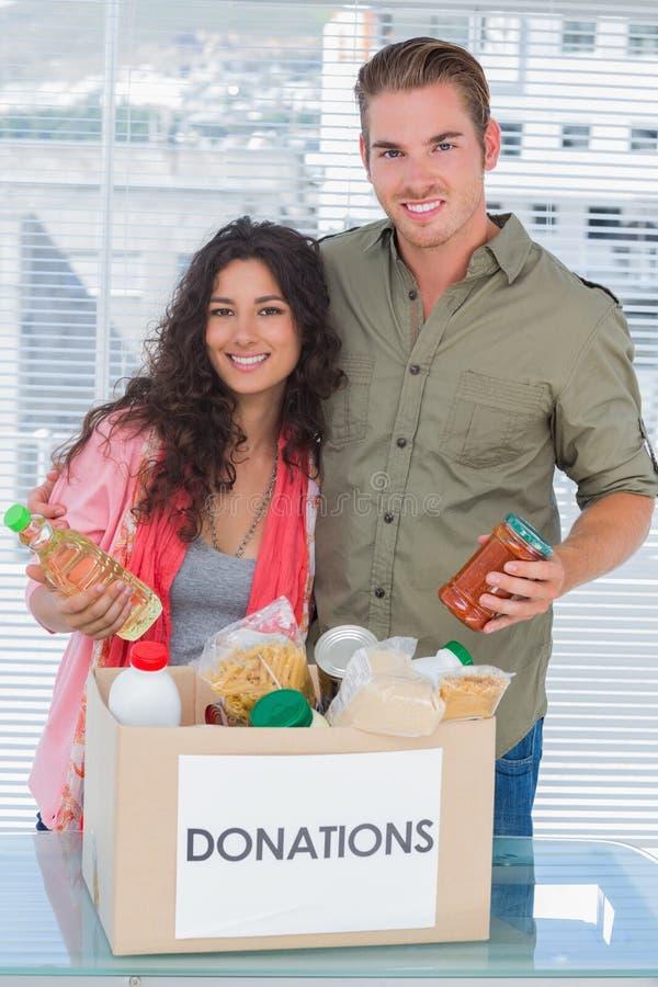 Sluit vrijwilligers die voedsel van schenkingendoos nemen royalty-vrije stock afbeelding