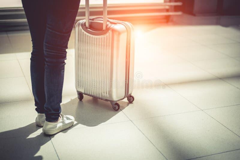 Sluit vrouw en koffer omhoog karretjebagage in luchthaven Mensen en levensstijlenconcept Reis en zakenreisthema Vrouw stock afbeelding