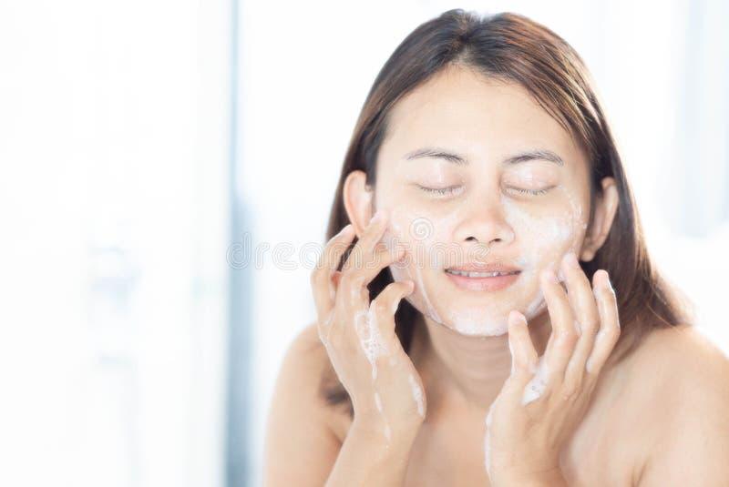 Sluit vrouw het kijken omhoog bezinning in de spiegel voor wasgezicht met schuim in het badkamers, gezondheidszorg en schoonheids stock afbeeldingen