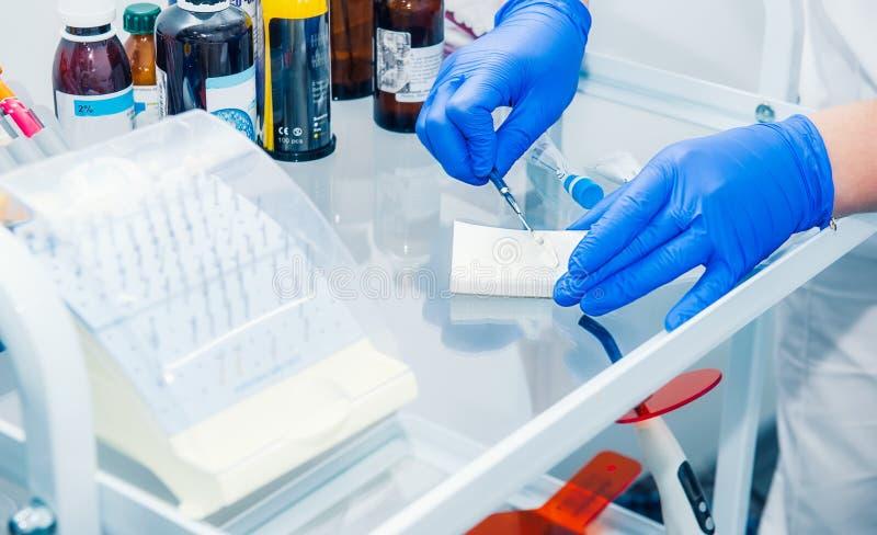 Sluit vrouwelijke medewerker voorbereidt omhoog materiaal voor behandeling, verdovingsmiddel bij tandkliniek Conc geneeskunde, st royalty-vrije stock afbeelding
