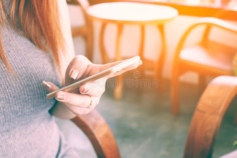 Sluit vrouwenhand het typen omhoog bericht op slimme telefoon in een koffie stock fotografie