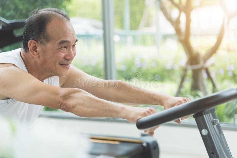 Sluit zich omhoog het hogere mens uitrekken op oefeningsmachine vóór workou stock afbeeldingen