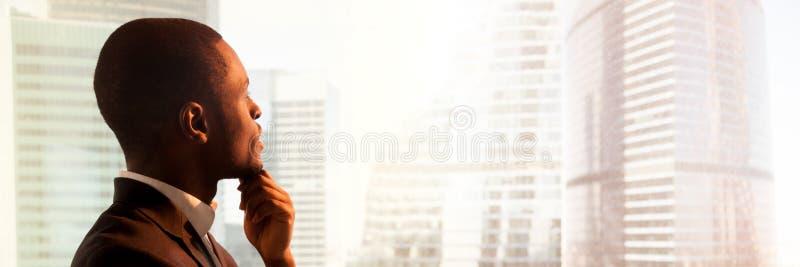 Sluit zijaanzicht omhoog zwarte zakenman status dichtbij venster het denken royalty-vrije stock afbeelding