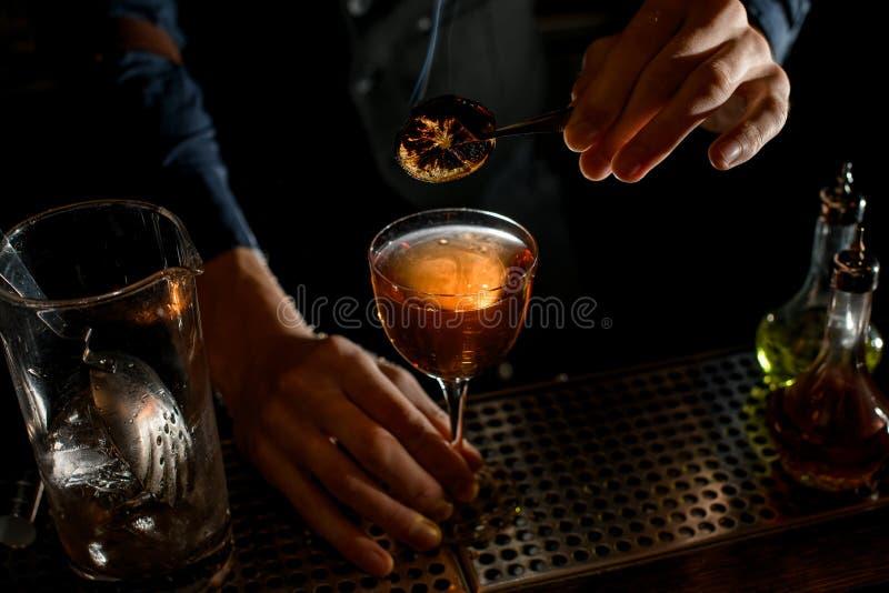 Sluiten Bartender houdt een pincet met een stukje citrus boven glas drank royalty-vrije stock afbeelding