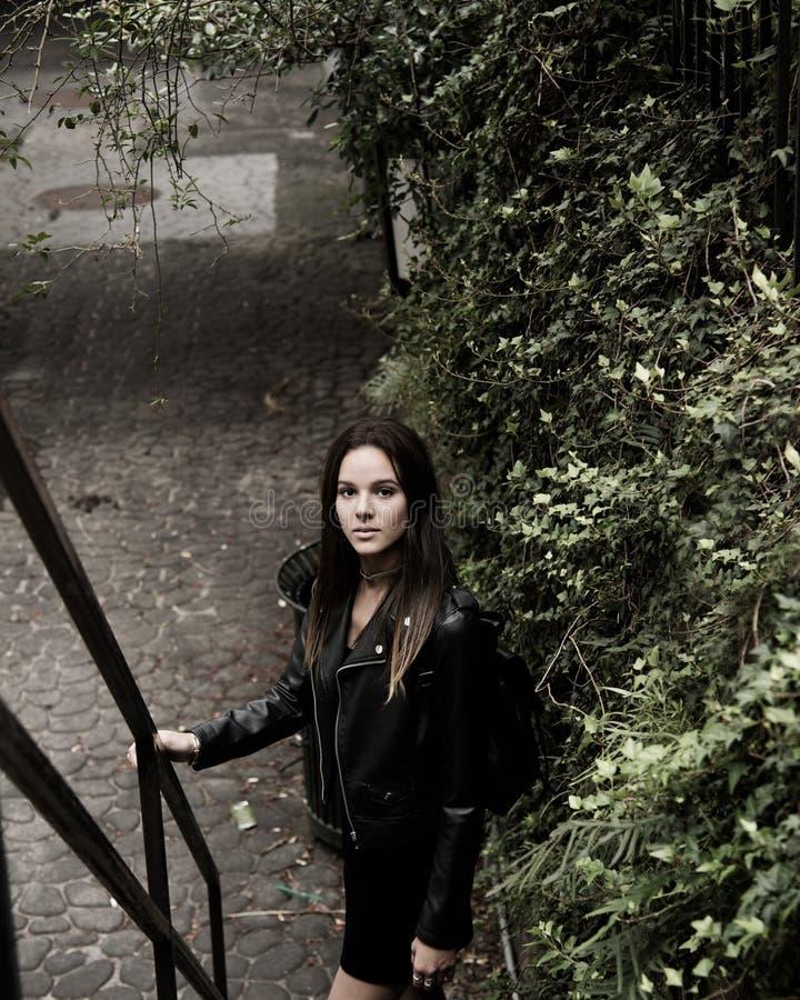 Sluiten Foto van vrouw met zwarte lederen jas die naast de trap staat stock afbeelding
