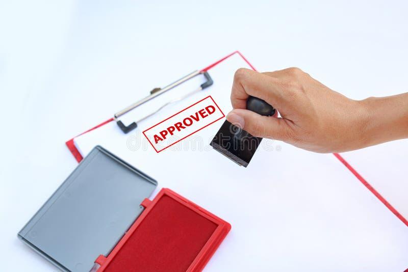 Sluiten hand-up Stamping Goedgekeurd op papier met rode Ink Padbox tegen witte achtergrond stock foto's