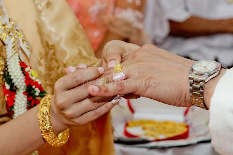 Sluiten-op de Thaise traditionele mens die trouwring op overeenkomstenproces zetten stock foto's