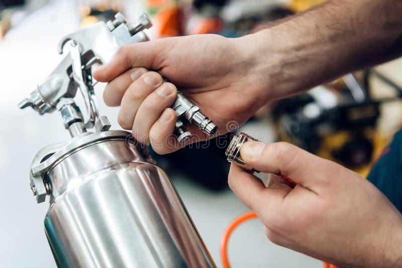 Sluiten Salesman stelt zich voor met een verfspuiter van compressor op voorgrond in de werktuigmachine royalty-vrije stock afbeelding