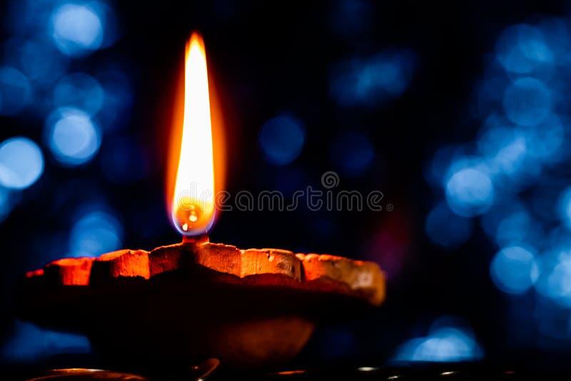 Sluiten van een gloeiende oorts Diya-terracotta lamp, vanuit een lage hoek met erect vlam en een blauwe achtergrond in omgevingsl royalty-vrije stock foto