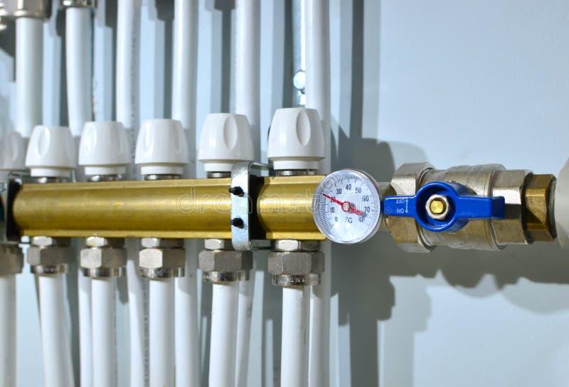 Sluiten van manometer, pijp, debietmeter, waterpompen en kleppen van verwarmingssysteem in een verwarmingsketelruimte thuis royalty-vrije stock afbeeldingen