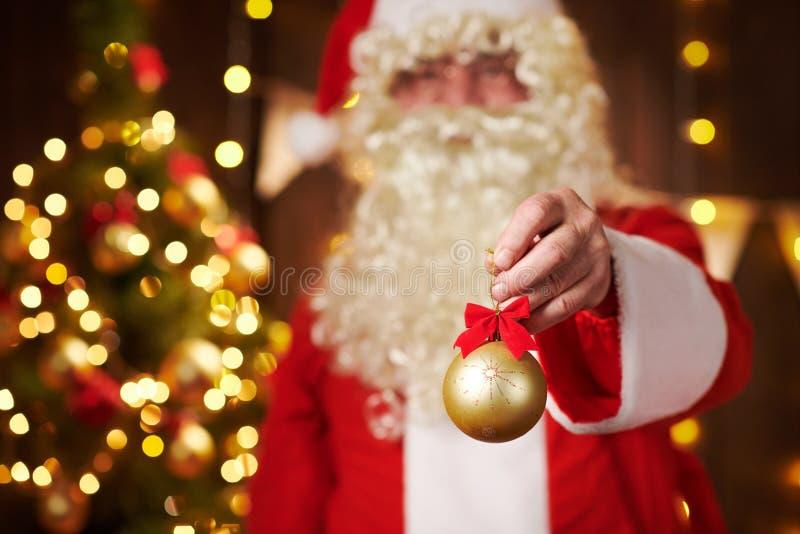 Sluiting van de handen van de kerstman met kerstbal versiering, binnenshuis in de buurt van de versierde kerstboom met licht - vr stock foto's