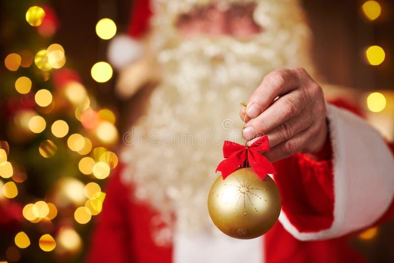 Sluiting van de handen van de kerstman met kerstbal versiering, binnenshuis in de buurt van de versierde kerstboom met licht - vr stock afbeelding
