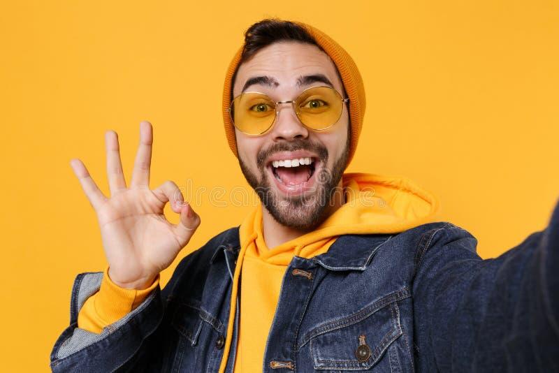 Sluiting van de hipster-man in de modejeans denim-kleren die geïsoleerd zijn op de gele oranje achtergrond Mensen die leven stock afbeeldingen
