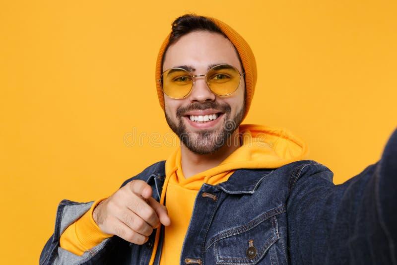 Sluiting van de hipster-man in de modejeans denim-kleren geïsoleerd op de gele oranje achtergrond Het begrip 'levensstijl' van me royalty-vrije stock foto