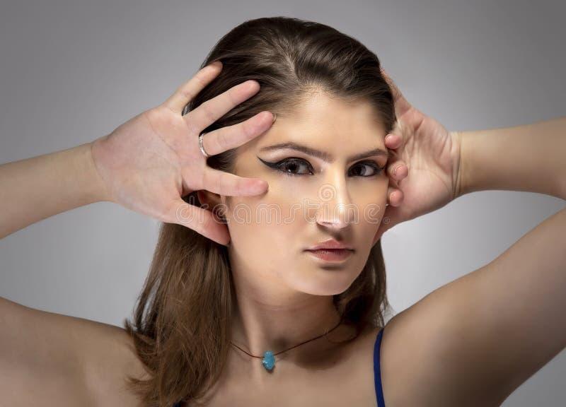 Sluiting van de mooie vrouw die de ogen van de liner verzint stock afbeelding